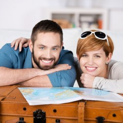 21109949 - portrait of happy couple with map leaning on suitcase in house